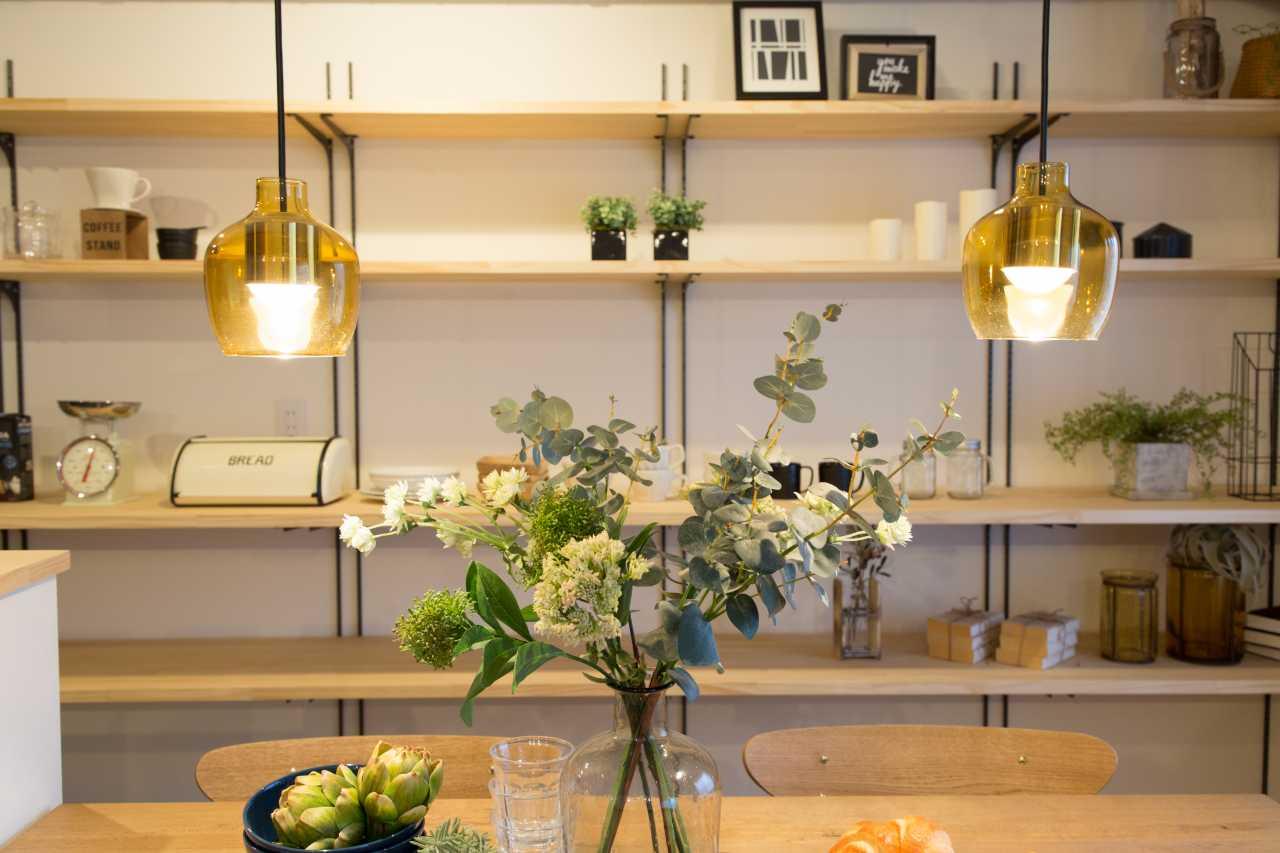 リビング~キッチンに繋がる壁には一面に可動棚を設置し、家具・家電で見せる収納を確保します。
