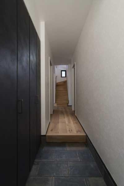玄関に入った瞬間に放出される解放感ある間取り。また、土間にタイルを敷き、断熱性能のよい玄関ドアに変更しました。そして、廊下は幅広のオークフローリングに変更し、右